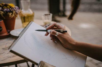 Poster activité dessin: main qui dessine un portrait sur un carnet de croquis.