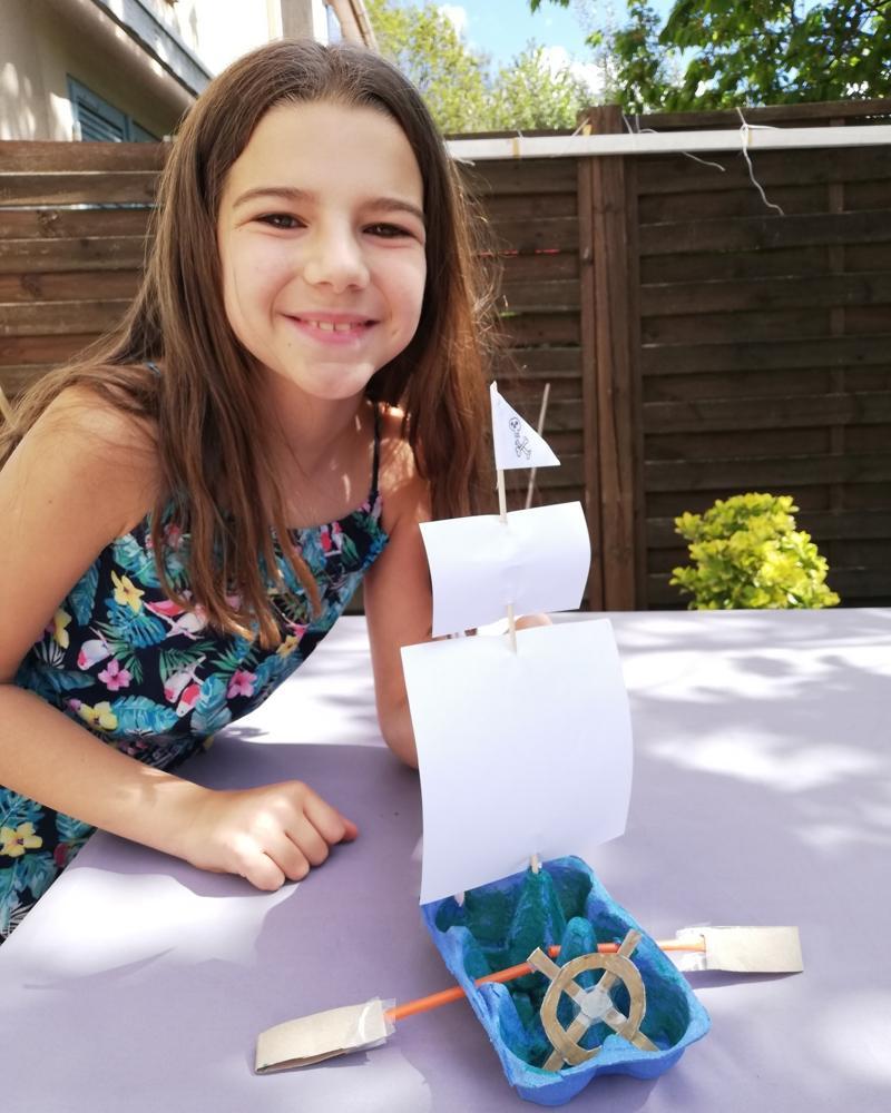 Résultat d'une activité: petite fille avec un bateau à voile construit dans une boite d'oeufs