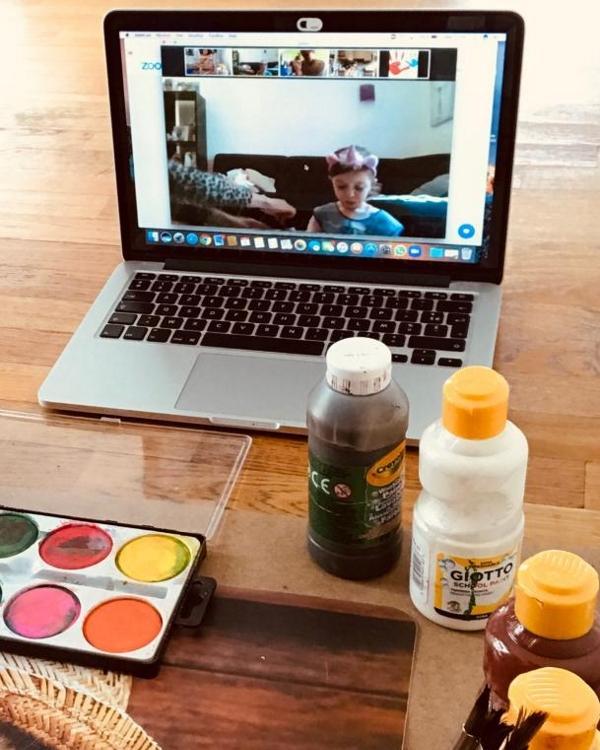 Ordinateur en visio sur une table, avec du matériel de peinture devant