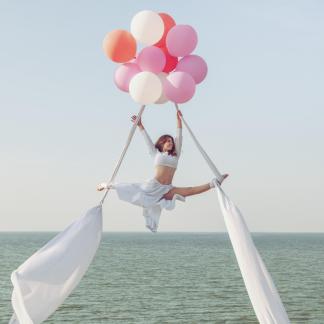 Jeune fille acrobate avec rubans et ballons, au dessus de l'eau