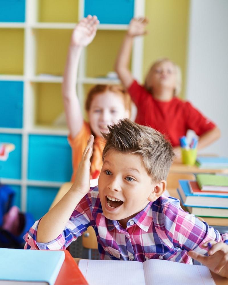 Enfants levant la main en classe